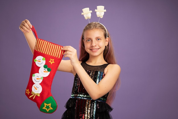 Happy little girl in glitter party dress and funny headband holding christmas stocking looking at camera smiling cheerfully standing over purple background