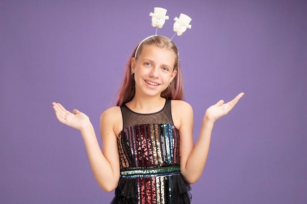 Happy little girl in glitter party dress and funny headband looking at camera smiling with arms raised standing over purple background