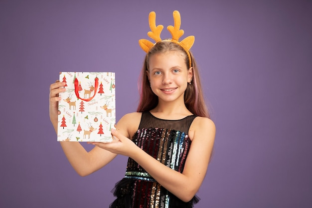 Happy little girl in glitter party dress and funny headband with deer horns holding christmas paper bag with gifts looking at camera smiling cheerfully standing over purple background