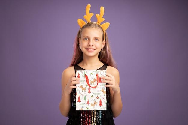 Bambina felice in abito da festa glitter e fascia divertente con corna di cervo che tiene un sacchetto di carta di natale con regali guardando la telecamera sorridendo allegramente in piedi su sfondo viola