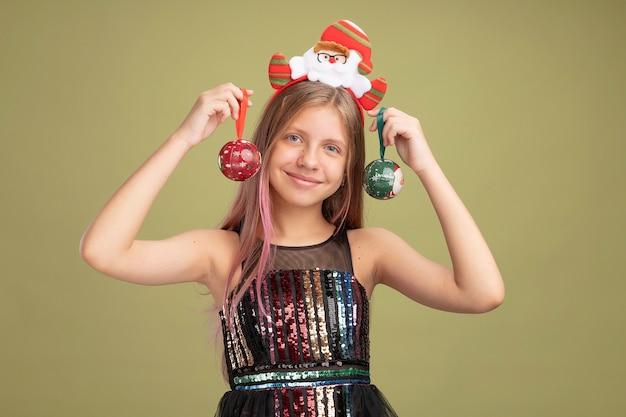 Bambina felice in abito da festa glitterato e fascia per capelli con babbo natale che tiene le palle di natale guardando la telecamera con un sorriso sul viso in piedi su sfondo verde