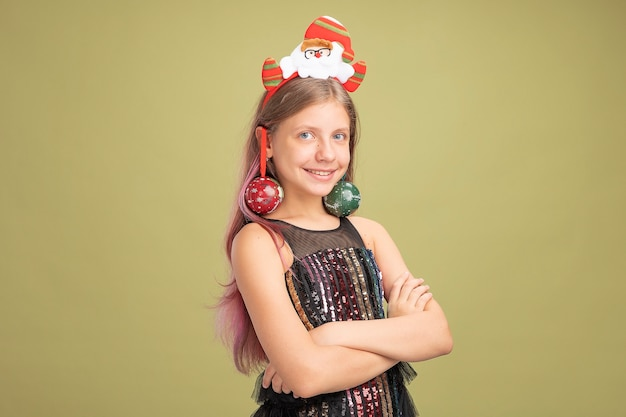 Happy little girl in glitter party dress and headband with santa with christmas balls on her ears looking at camera smiling standing over green background