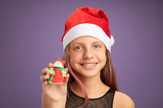 Happy little girl in glitter party dress and santa hat holding christmas toy looking at camera smiling cheerfully standing over purple background