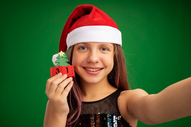 Happy little girl in glitter party dress and santa hat holding toy cubes with new year date looking at camera smiling cheerfully standing over green background