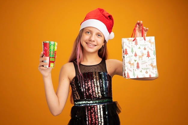 Happy little girl in glitter party dress and santa hat holding two colorful paper cup and paper bag with gifts looking at camera with smile on face standing over orange background