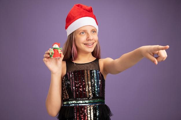 Felice bambina in abito da festa glitter e cappello da babbo natale che mostra il giocattolo di natale che guarda da parte puntando con il dito indice a qualcosa sul lato in piedi su sfondo viola