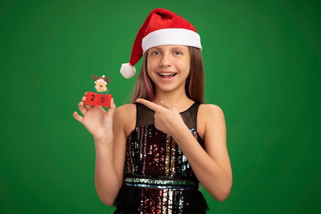 Happy little girl in glitter party dress and santa hat showing toy cubes with date twenty five pointing with index finger at them smiling cheerfully standing over green background