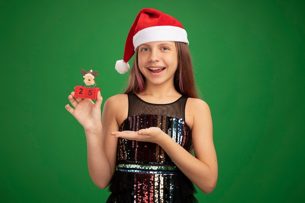 Happy little girl in glitter party dress and santa hat showing toy cubes with date twenty five presenting with arm of her hand smiling cheerfully standing over green background