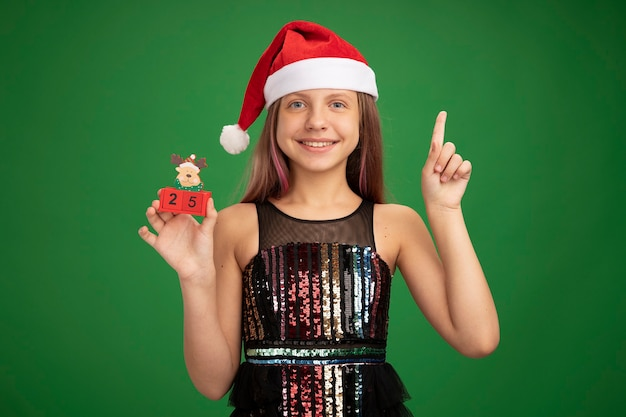 Happy little girl in glitter party dress and santa hat showing toy cubes with date twenty five showing index finger smiling cheerfully standing over green background