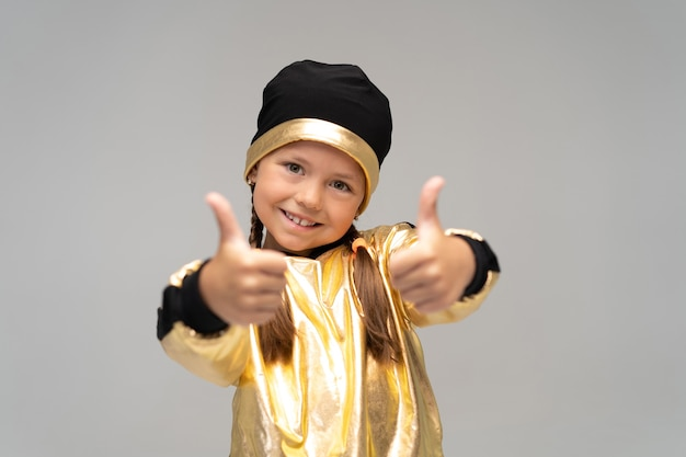 Happy little girl in gold suit dancing isolated on white surface