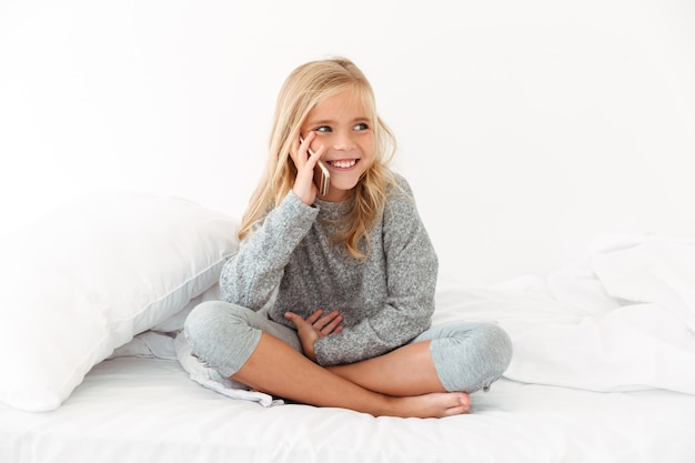 Happy little girl in gray pajamas talking on smartphone, looking aside while sitting on bed