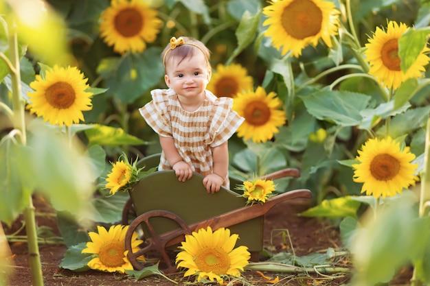 カートで太陽の穏やかな光線の下で咲くひまわりの中で楽しんで幸せな少女