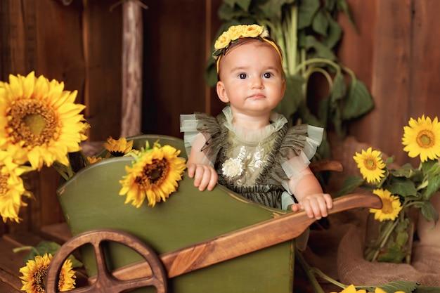 楽しんで、カートの近くに咲くひまわりの中で遊んでの幸せな女の子