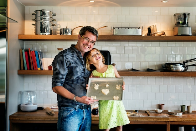 Happy little girl and her father baking concept