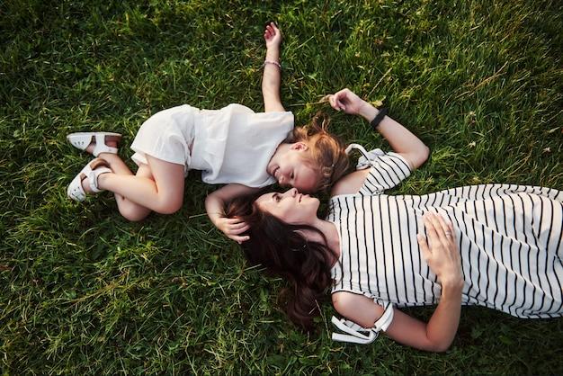Bambina felice e sua madre divertendosi all'aperto sull'erba verde nel giorno di estate soleggiato.