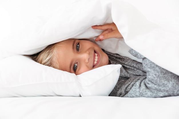 Happy little girl hiding under the blanket,