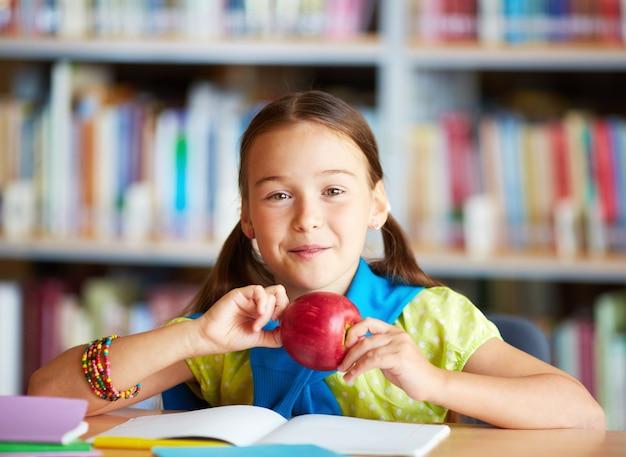 Happy little girl holding an apple