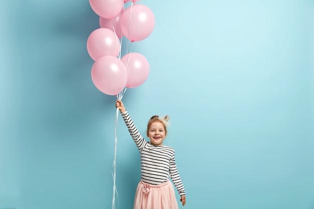 Bambina felice che tiene palloncini