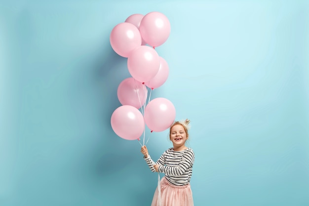 Happy little girl holding balloons
