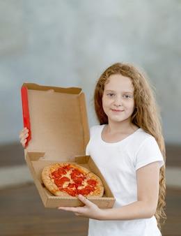 Счастливая маленькая девочка, держащая коробку с пиццей пепперони.