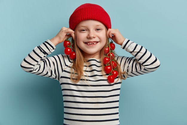 Bambina felice che tiene i pomodorini