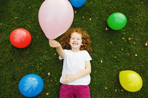 Happy little girl holding colored balloon, lies on green grass at summer park.