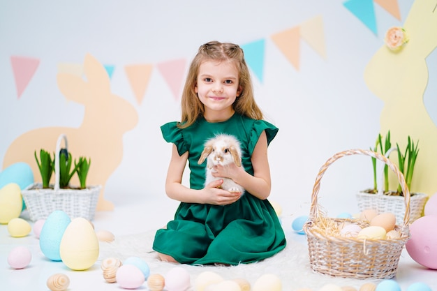Happy little girl holding cute fluffy bunny near painted easter eggs