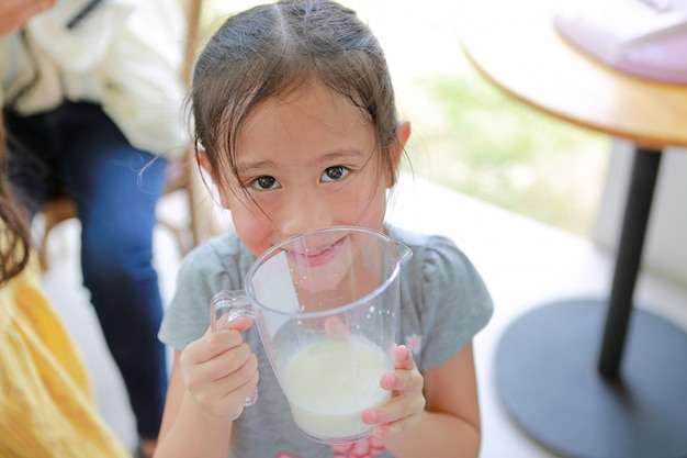 Happy little girl holding glass of fresh milk from the cows in dairy production farm.