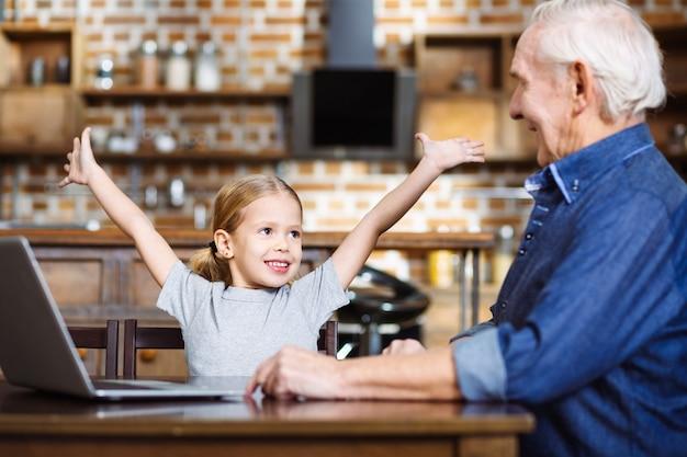 Счастливая маленькая девочка, держащая руки вверх, чувствуя себя счастливой со своим дедом