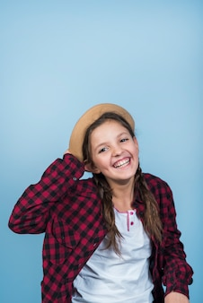 Happy little girl holding hat on head