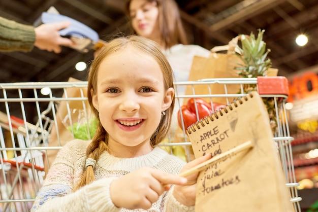 Счастливая маленькая девочка держит список покупок