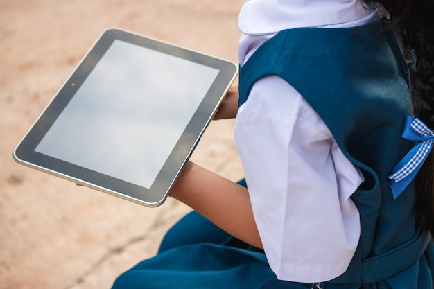 Happy little girl holding tablet pc outdoors in summer park