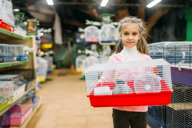 Happy little girl holds cage for hamster in pet shop. petshop advertising concept