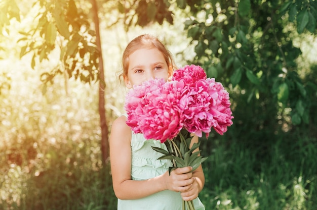 Happy little girl holds in her hands a bouquet of pink peony flowers in bloom