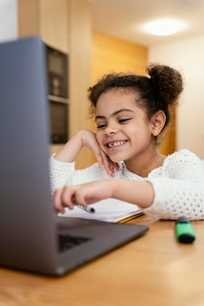 Happy little girl at home during online school with laptop