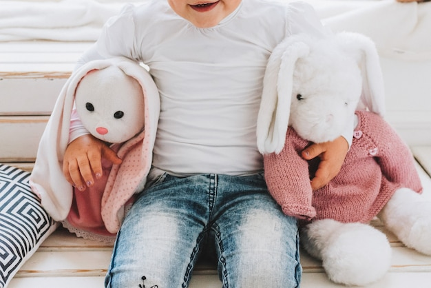 Happy little girl hugging her plush bunny toys