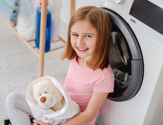 Счастливая маленькая девочка обнимает плюшевого мишку в полотенце после стирки на стиральной машине