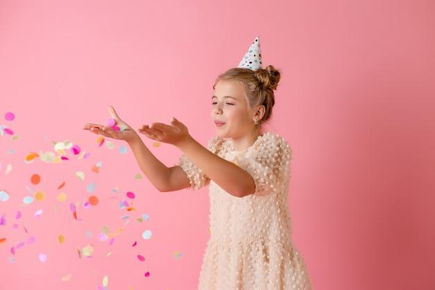 생일 모자에 행복 한 어린 소녀는 스튜디오에서 분홍색 배경에 그녀의 손바닥 여러 가지 빛깔의 색종이를 불면