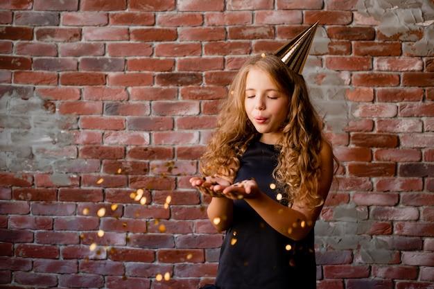 彼女の誕生日の帽子をかぶった幸せな少女は紙吹雪の手のひらから吹き飛ばされます