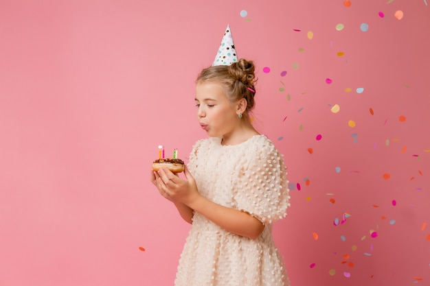 Счастливая маленькая девочка в шапке на день рождения загадывает желание и задувает свечи на торте.
