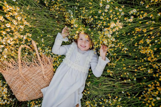 綿のドレスを着た幸せな少女は、日没の夏にデイジーのフィールドに横たわっています。笑い、上からの眺め