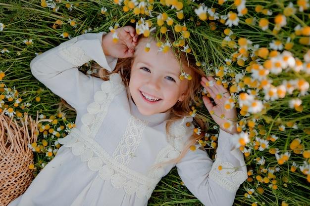 Счастливая маленькая девочка в хлопковом платье лежит в поле маргариток летом на закате. смеется, вид сверху