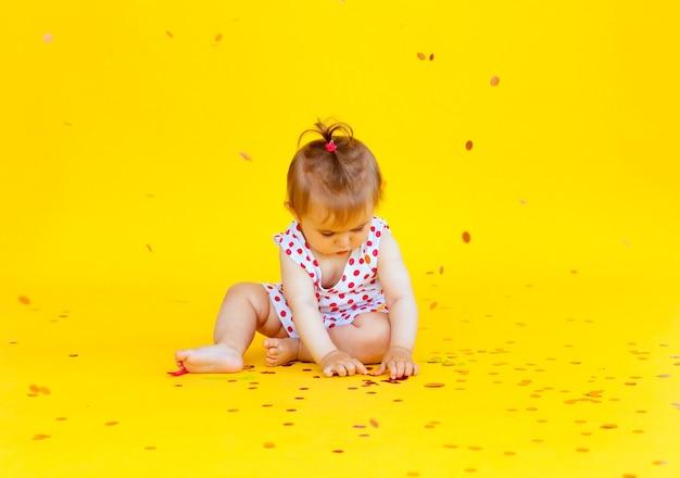 エンドウ豆のドレスを着た幸せな少女は、黄色の背景に紙吹雪をキャッチします。テキストの場所