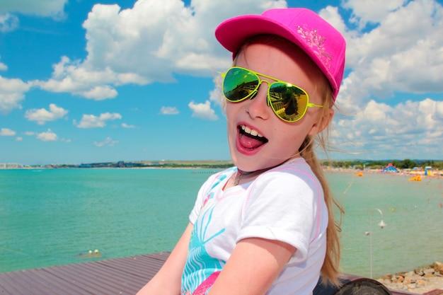 日当たりの良い黄色いメガネと夏の海のピンクの帽子の幸せな少女。