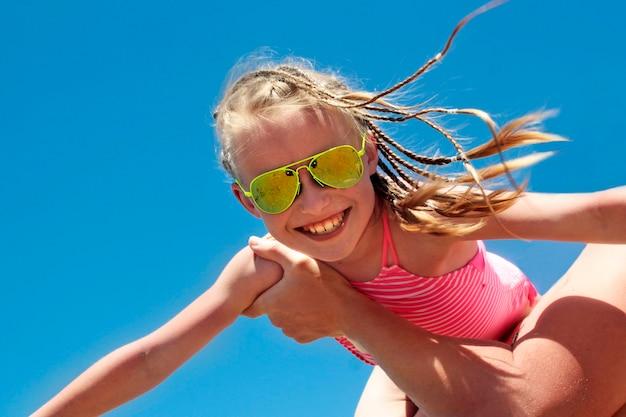 Счастливая маленькая девочка в солнечно-желтом цвете с очками и косичками на голове и на руках отца на летнем море.