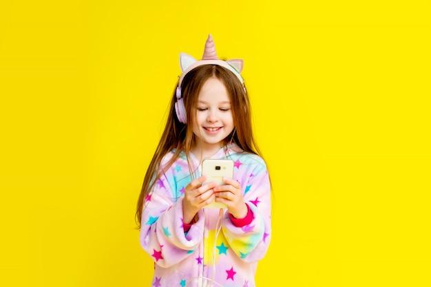 Счастливый маленькая девочка в единорог кигуруми на желтом фоне