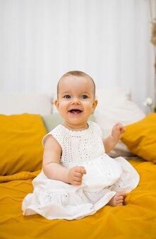 Счастливая маленькая девочка в белом хлопковом платье сидит на кровати с желтым покрывалом