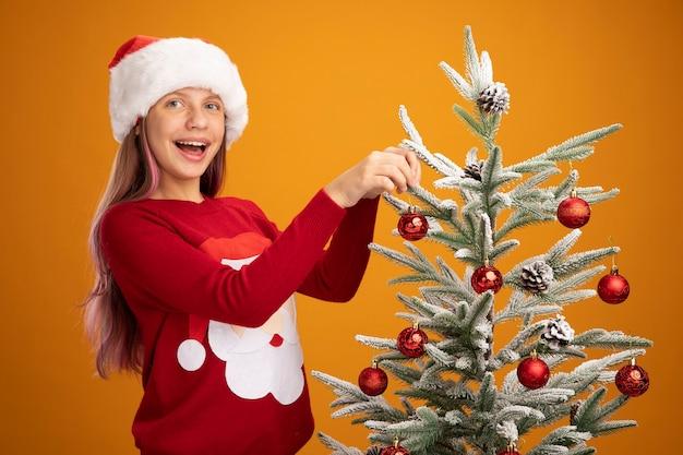 オレンジ色の背景の上で元気に笑ってクリスマスツリーにボールをぶら下げてクリスマスセーターとサンタ帽子の幸せな少女