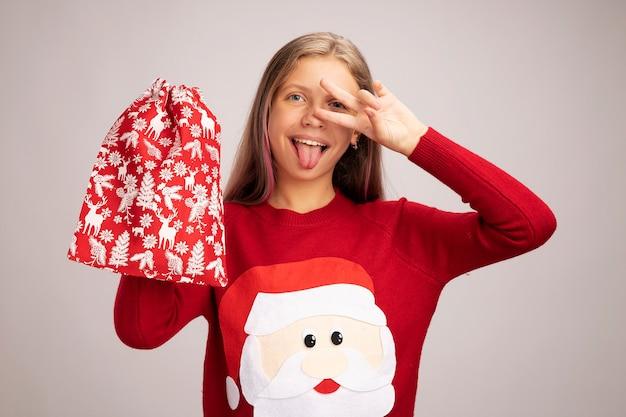 Счастливая маленькая девочка в рождественском свитере держит красную сумку санта-клауса с подарками, глядя в камеру, весело улыбаясь, показывая знак v рядом с глазами, торчащими языком, стоя на белом фоне