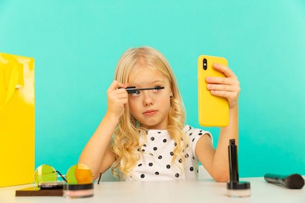 비디오 블로그에 대한 비디오를 만드는 전화 카메라 앞에서 행복 한 어린 소녀. 블로거로 일하면서 인터넷 용 비디오 튜토리얼 녹화.